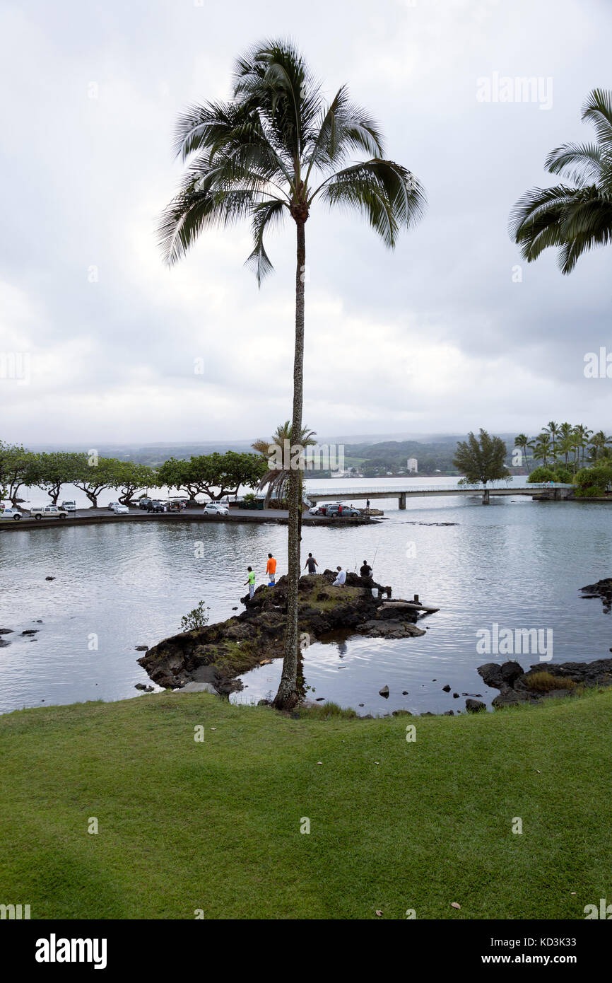 Fishermen fishing the calm waters of Hilo Bay at dusk, with a view of Coconut Island. - Stock Image