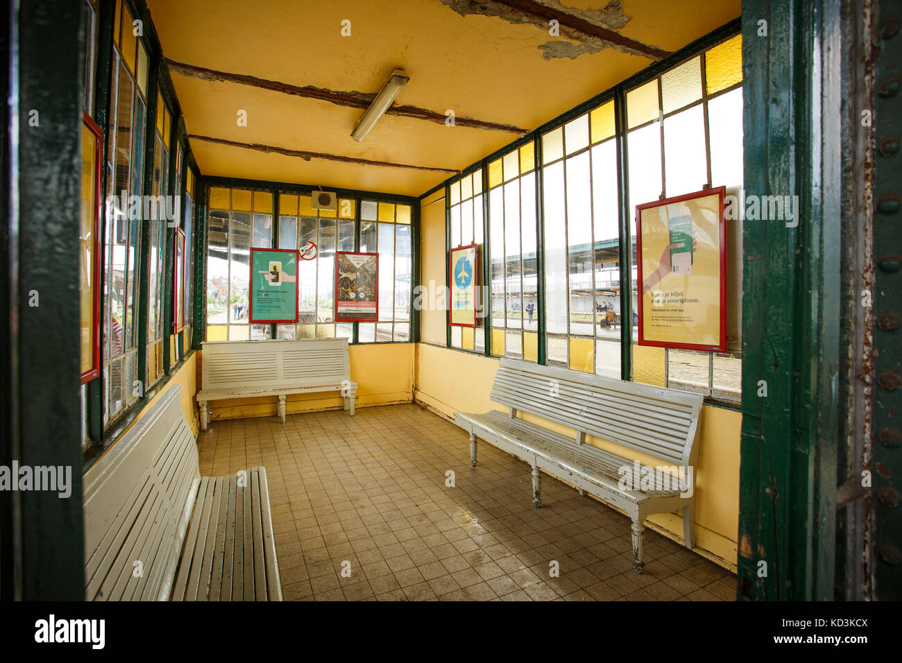 Detail picture of an empty yellow waiting room in Ghent Sint Pieters Train Station with green iron columns, three - Stock Image