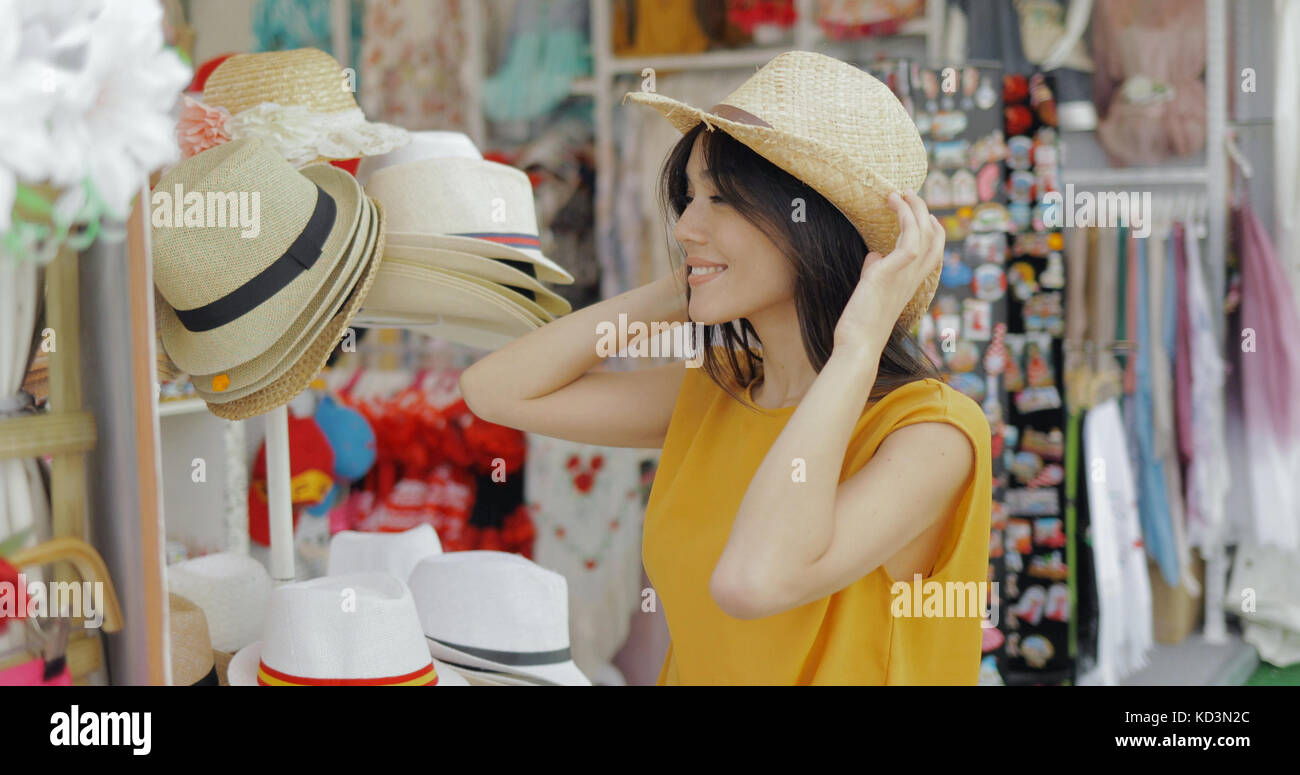 Charming model trying on hats in shop - Stock Image