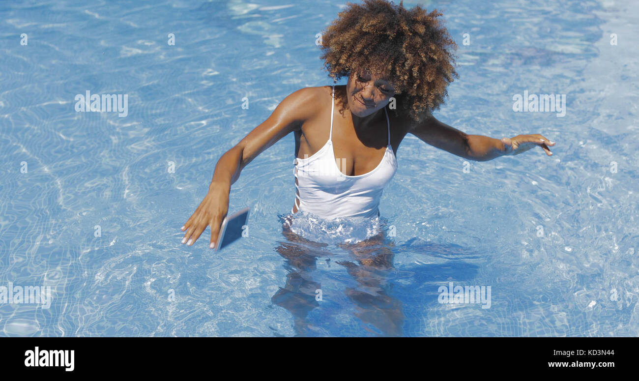 Woman dropping phone in pool - Stock Image