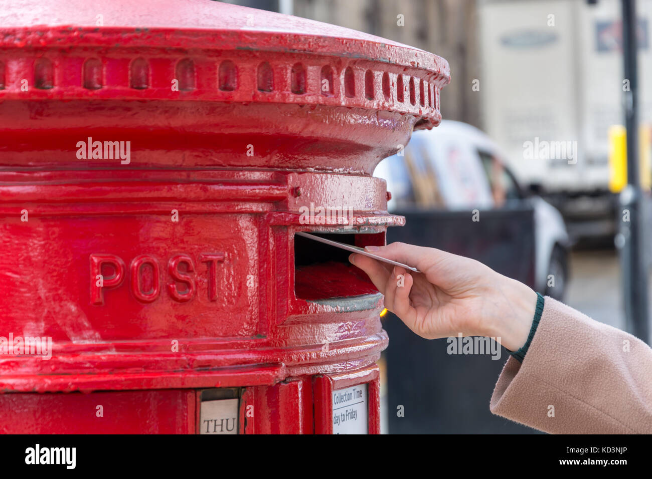 Throwing a letter in a red British post box from the side - Stock Image
