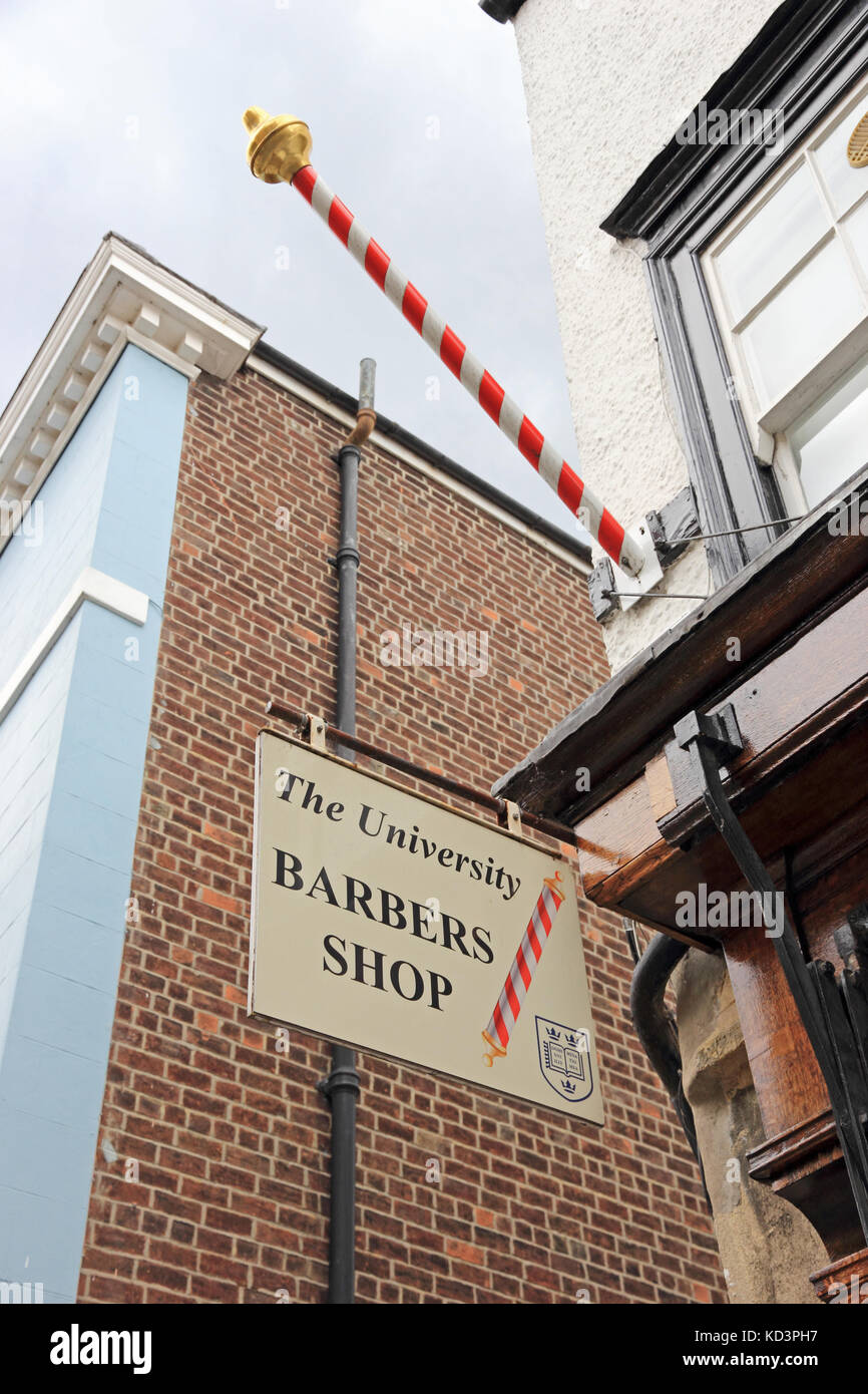 The University Barbers Shop sign, with traditional red and white striped pole, Oxford, UK - Stock Image