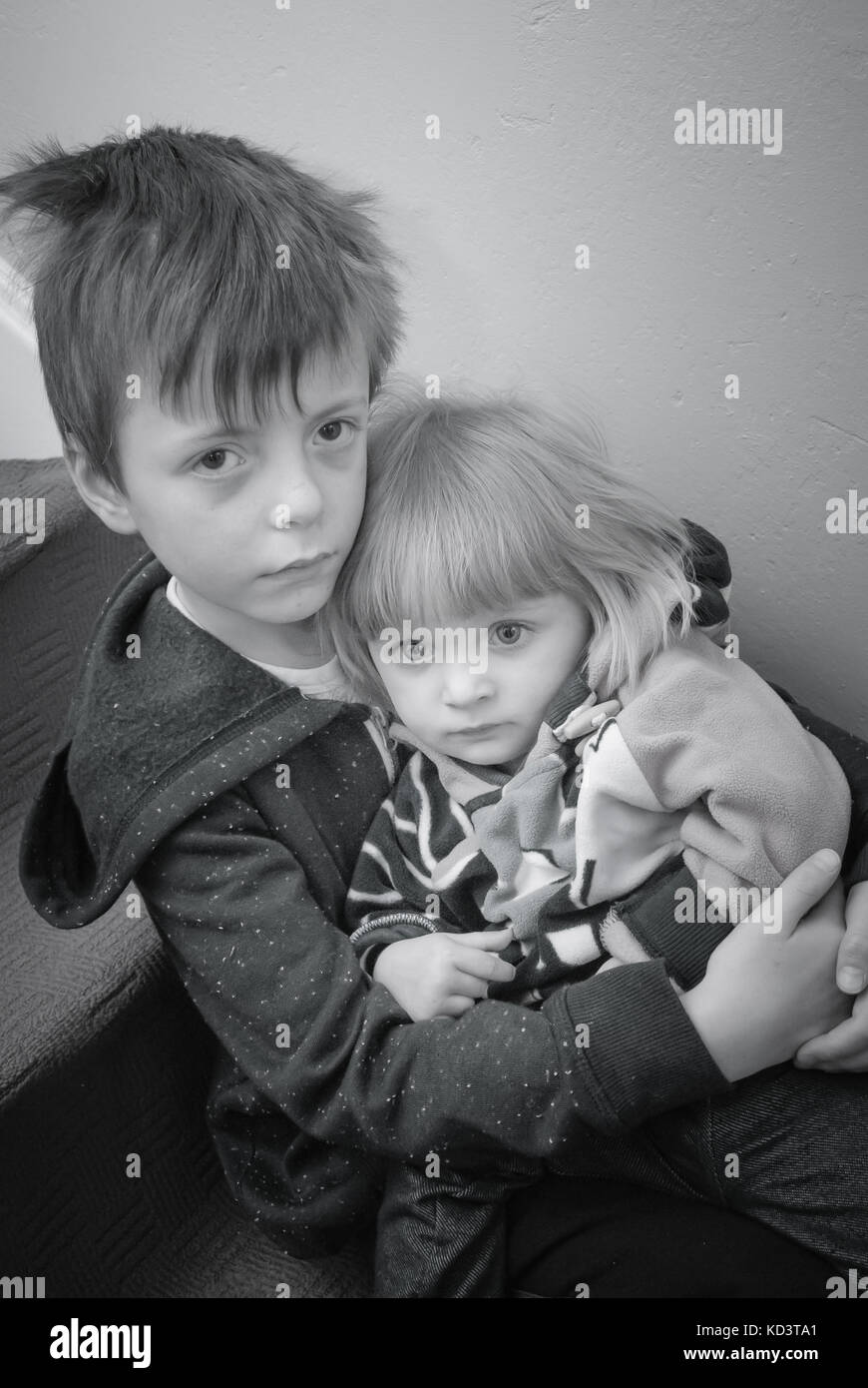 A conceptual black and white image of two siblings  representing a range of concepts such as poverty, abuse,loneliness. - Stock Image