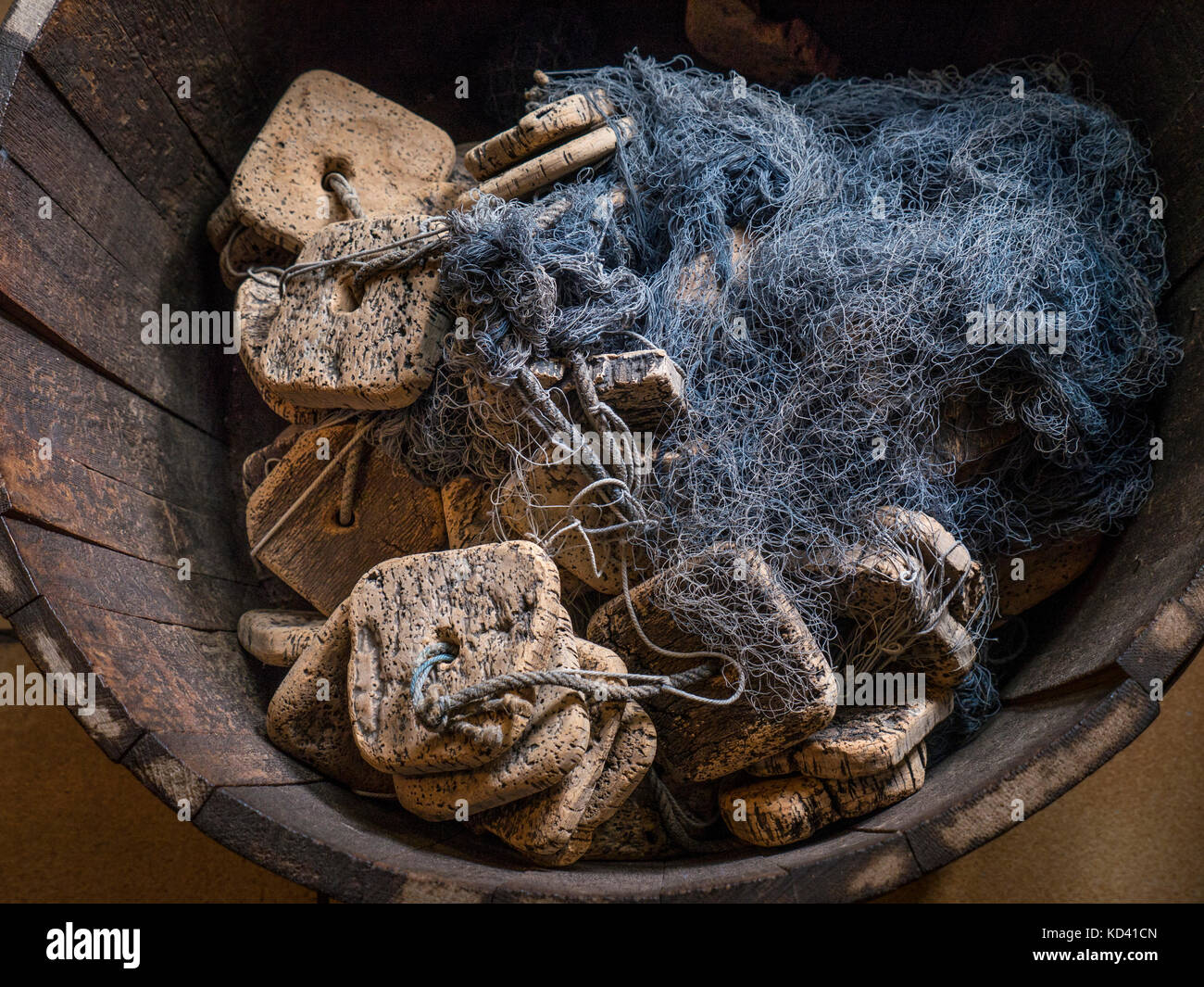 Old Cork fishing floats and netting discarded in wooden fishery tub - Stock Image