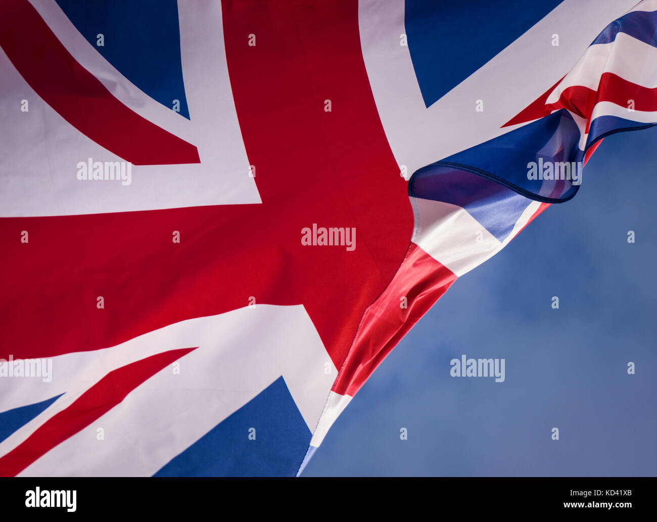 Union Jack Flag flying against blue sky with breeze blowing through as metaphor concept for Borders Brexit Immigration Stock Photo