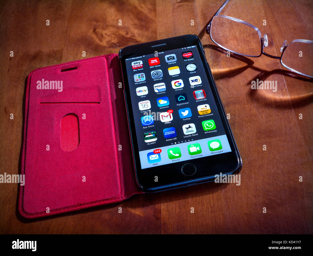 iPhone 7 Plus Piano Black Glossy with screen apps, in red leather flip-open case placed on table in shaft of light - Stock Image
