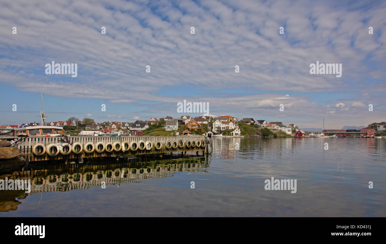 Wooden poles and car tires of a pier reflecting in the water and island with traditional houses behind on Hundvåg, - Stock Image