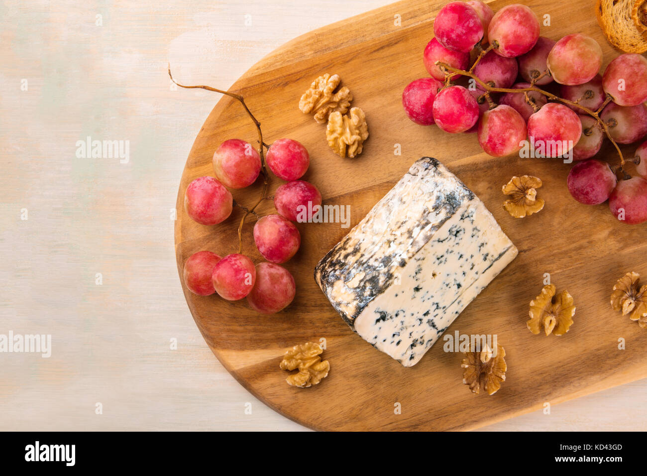 Blue cheese with grapes, nuts, and toasts, and copyspace - Stock Image