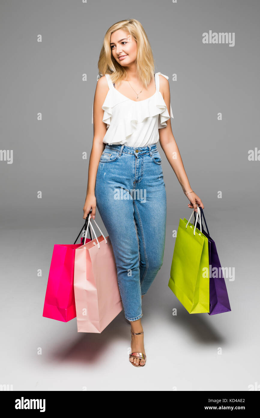 Happy woman enjoying successful shopping. Woman with shoping bags on white. Stock Photo