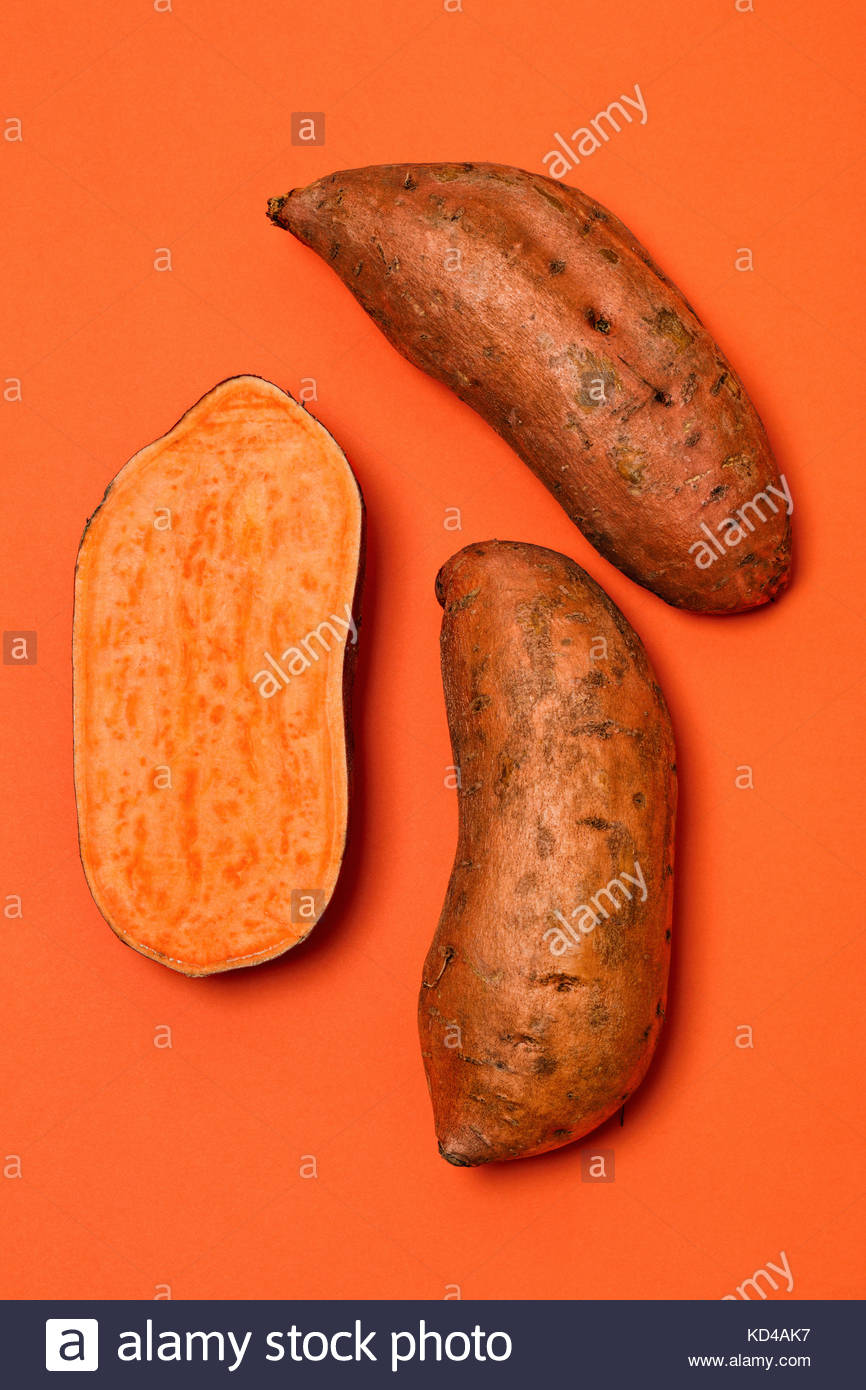 Whole and halved sweet potatoes on an orange background. They are a root vegetable rich in fibers and vitamins, - Stock Image