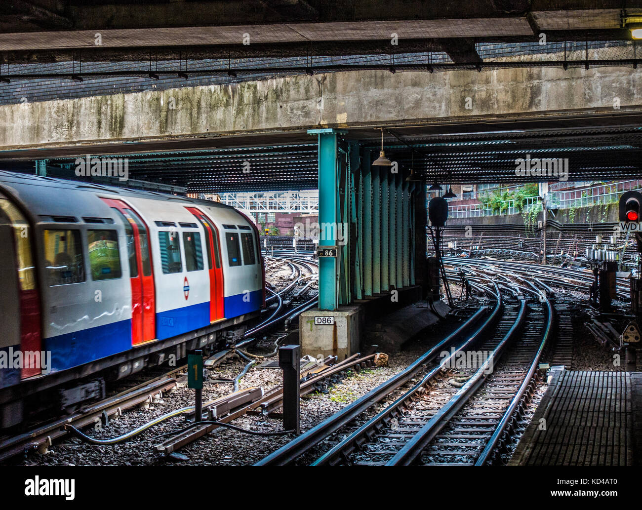 London Underground tube train on the line tracks, just leaving an overground station, despite most of the route Stock Photo