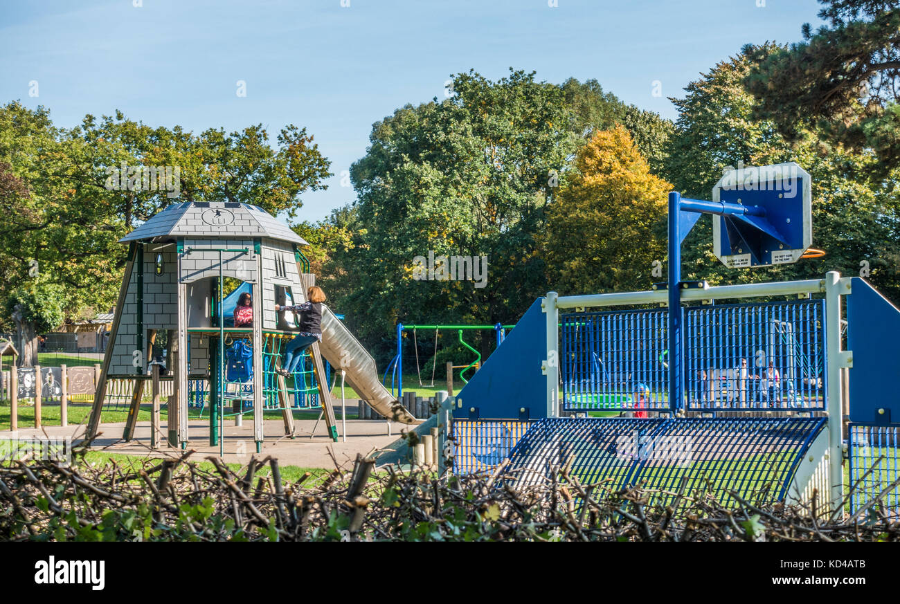 Children's playground / play area, with two children on a climbing frame on a warm sunny day early autumn. Gunnersbury - Stock Image
