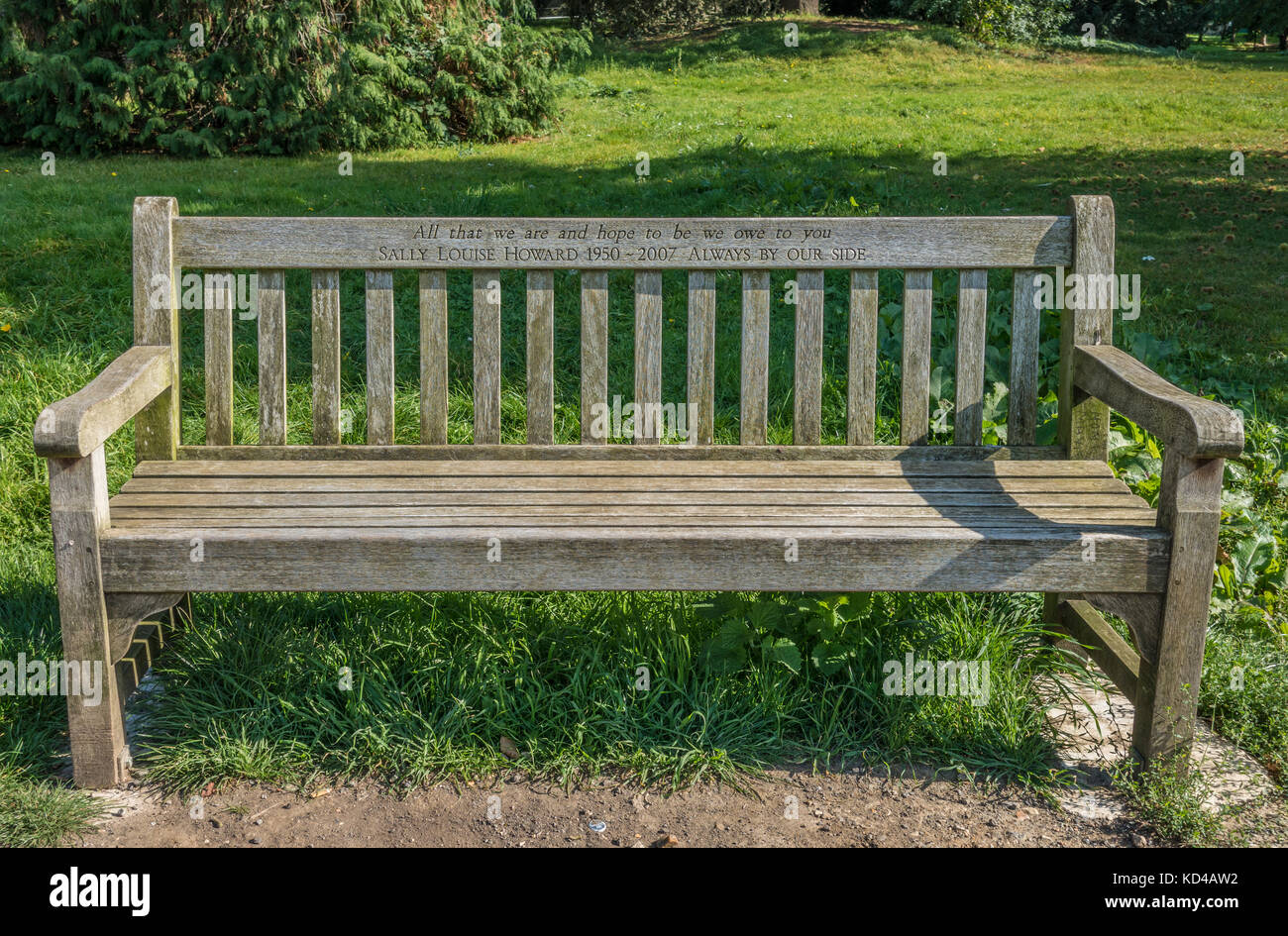 Sturdy wooden bench, engraved with tribute to the person in whose name it was erected in remembrance. Gunnersbury - Stock Image
