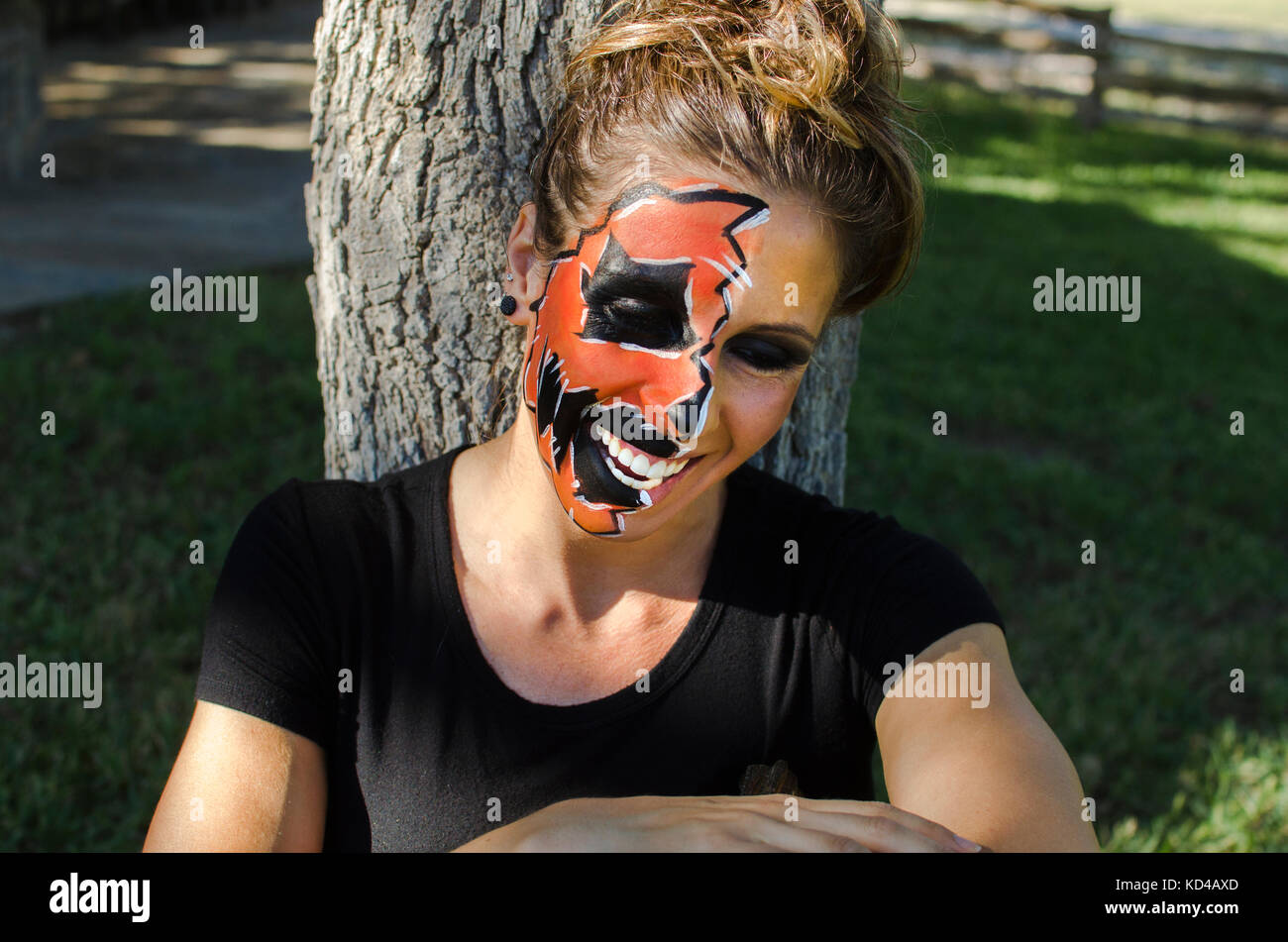 Woman in Jack-O-Lantern face paint looks happy and festive for the Halloween fall holiday. - Stock Image