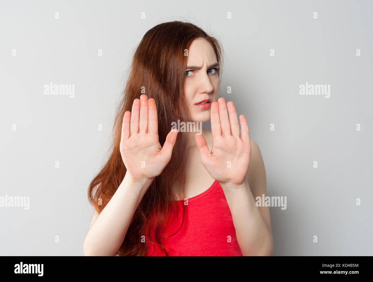 A frightened annoyed young woman holds her hands in front of her making stop sign, defending herself from someone - Stock Image
