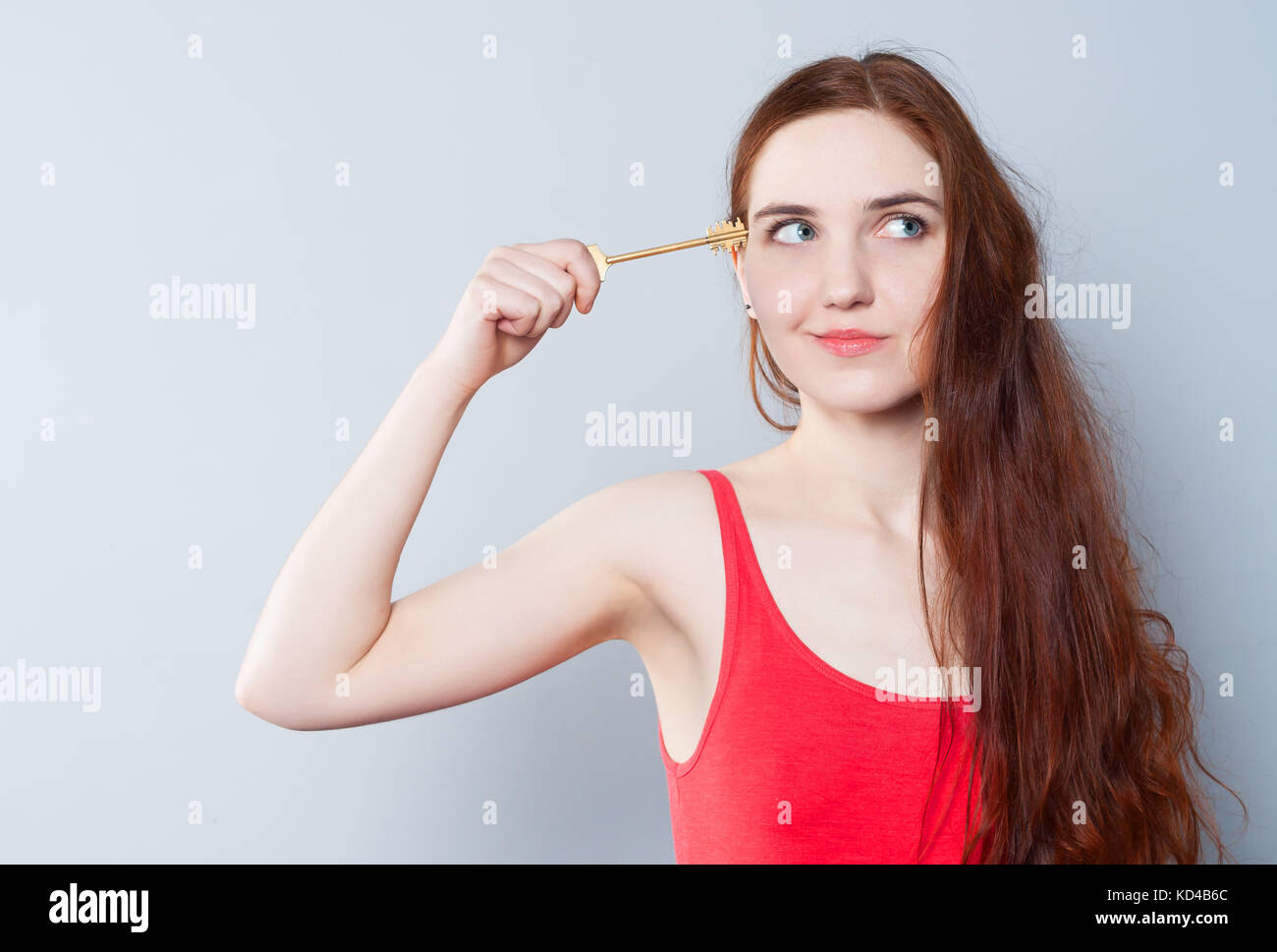 A young cute woman holds a big key next to her head, trying to open her mind or head. The concept of creativity, - Stock Image