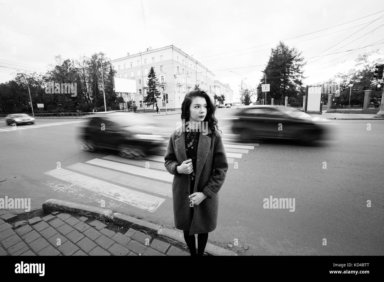 One teenage girl blue coat standing at the traffic light on city street on a cloudly autumn day with vehicles passing - Stock Image