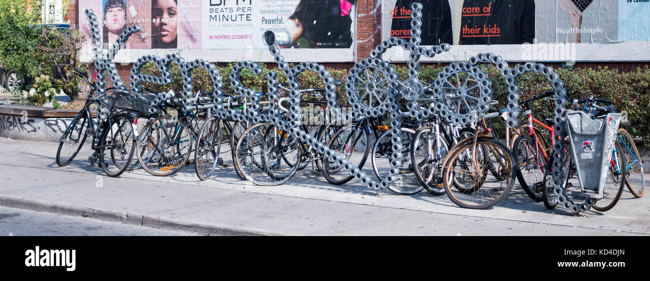 Bicycle rack shaped like bicycle chain spelling Kensington in Kensington Market in downtown Toronto Ontario Canada - Stock Image