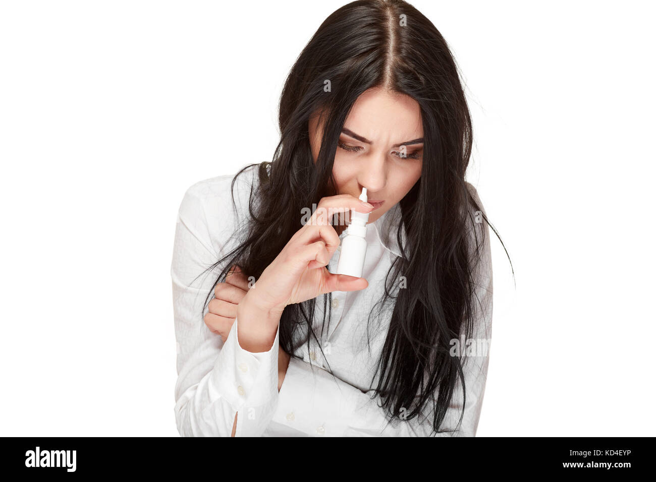 Portrait of unhealthy brunette girl using and drown spray for nose, anti virus, flu medicament. Illness,virus, respiration - Stock Image