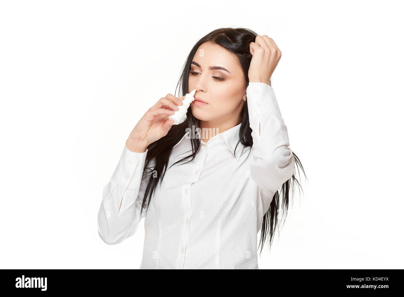 View od sad unhealthy brunette woman with long hair, holding head by hand and drown nasal spray in nose. Home therephy - Stock Image