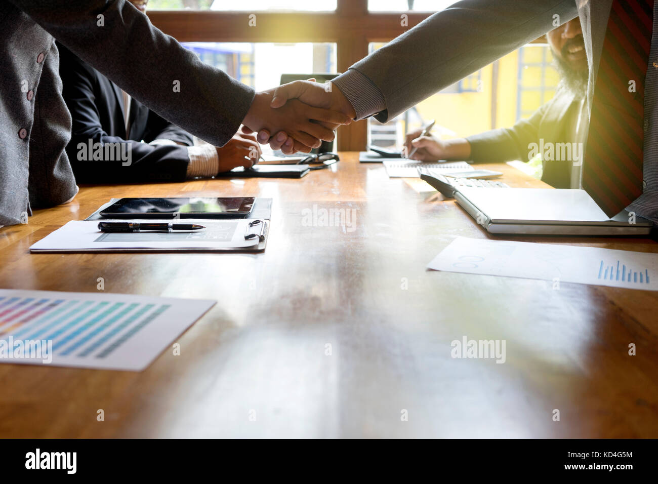 Group of businessman handshake  on wood table with computer - Stock Image