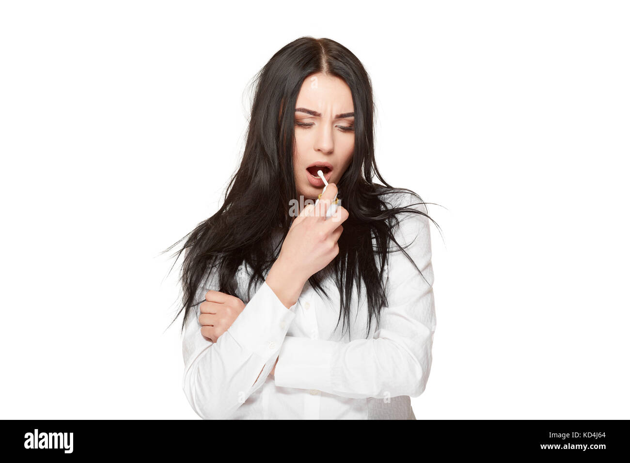 Studio portrait of brunette girl on white, holding and using spray for throat, anti flu medicament. Concept of illness,virus, - Stock Image