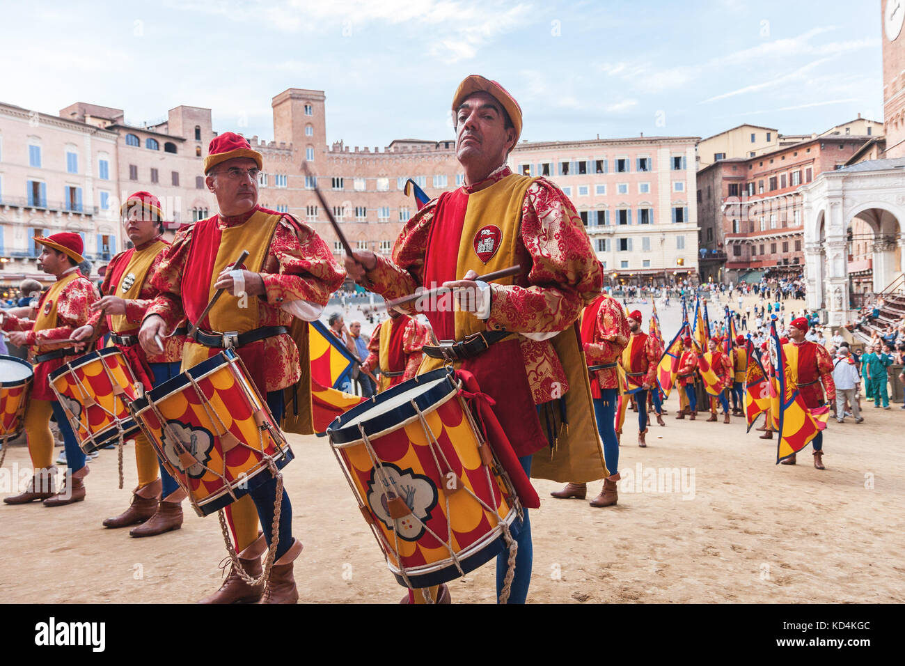 Men musicians with drums in historical colorful costumes celebrating at traditional Palio horse race parade in Siena, Stock Photo