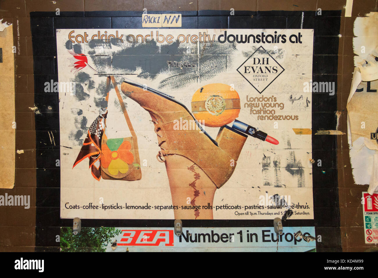 Vintage advertising posters for DH Evans and BEA on wall in old closed underground station, London - Stock Image