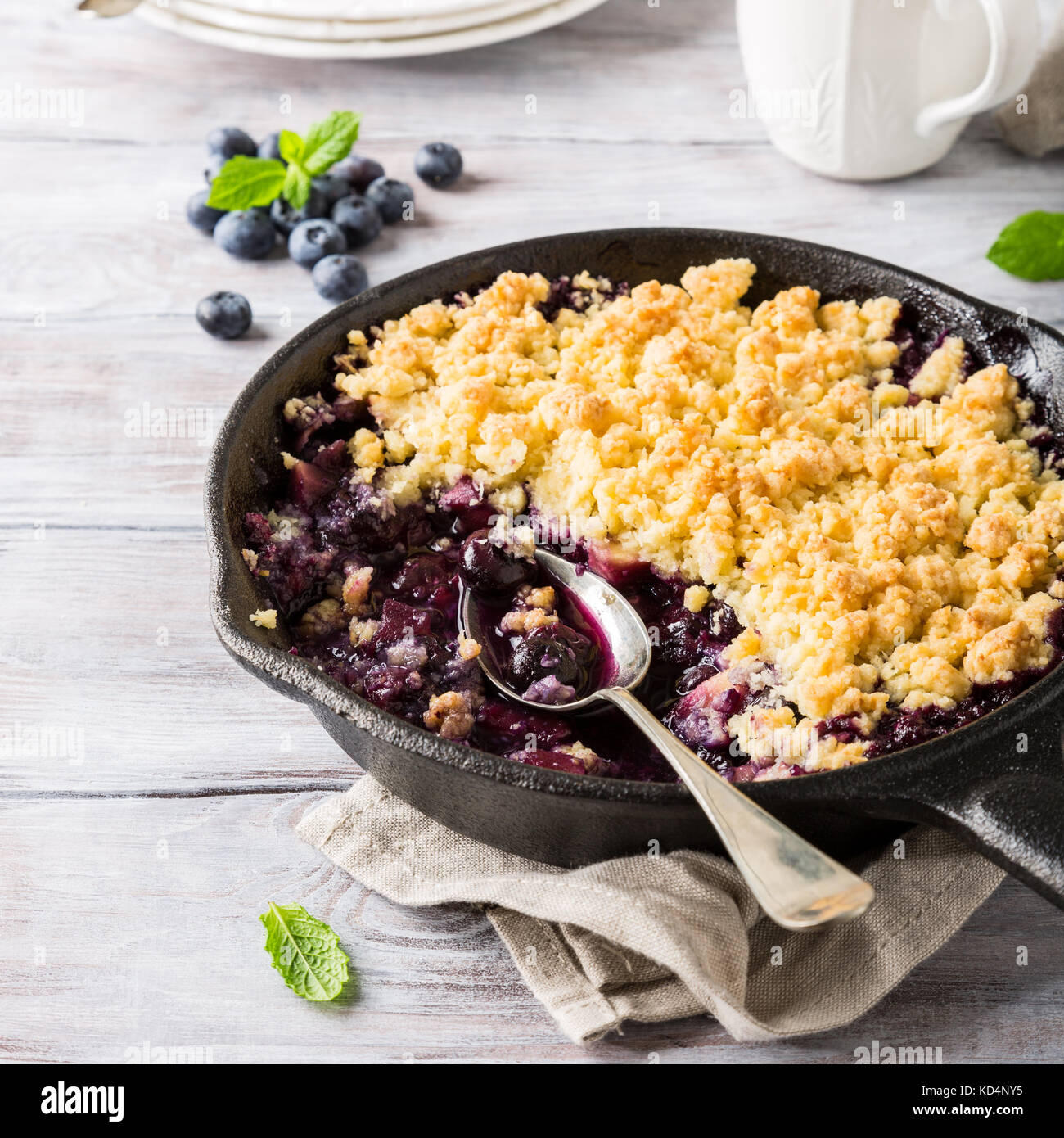 Coconut crumble in cast iron pan with fresh apples and blueberry. Healthy food concept. Stock Photo