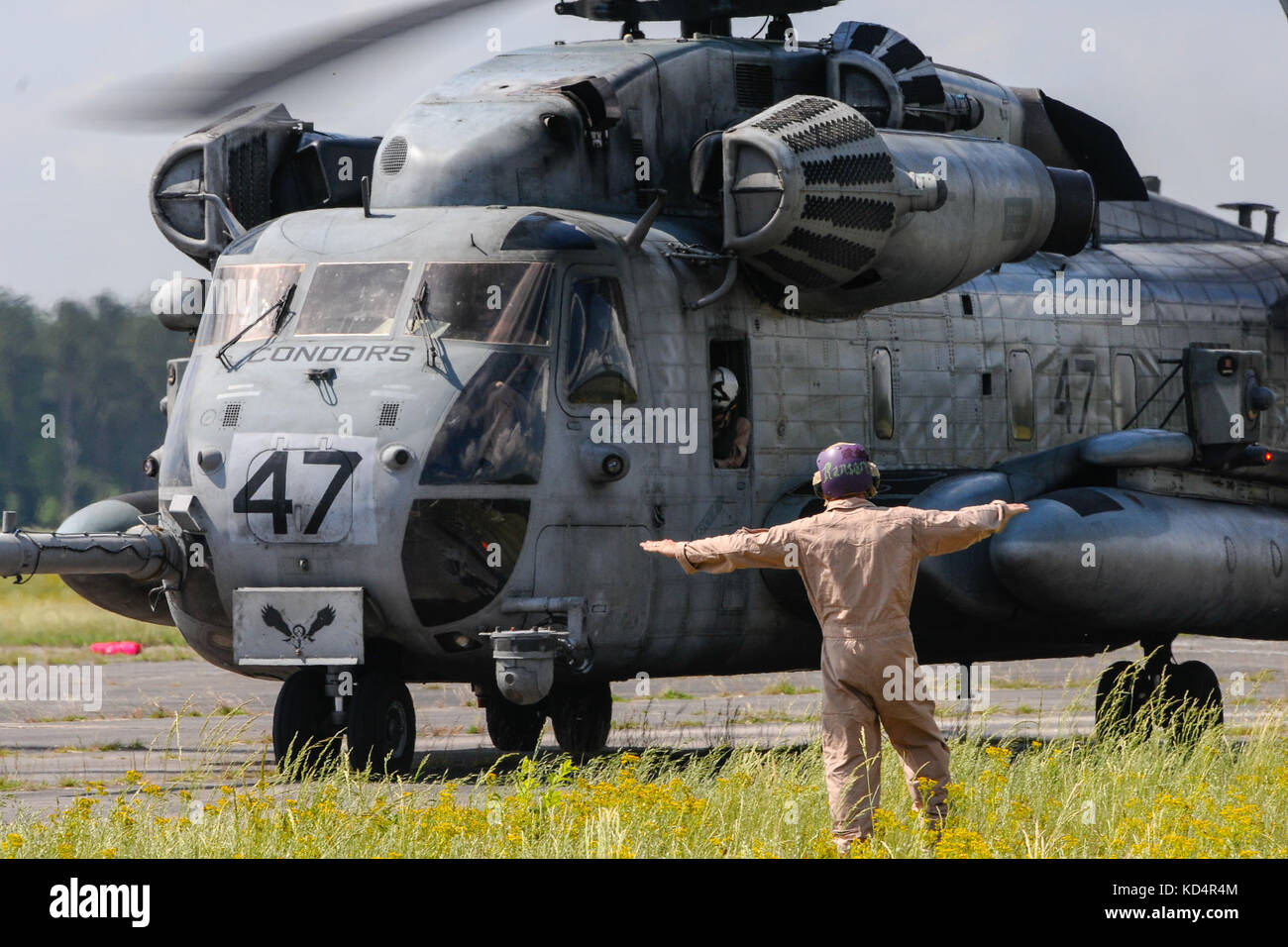 A U.S. Marine assigned to the 273rd Marine Wing Support Squadron, Air Operations Company, marshals a CH-53 Sea Stallion - Stock Image