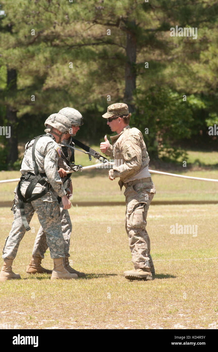 A U.S. Army Soldier assigned to Alpha Company, 2nd Battalion, 7th Special Forces Group (Airborne) verifies Soldiers assigned to the 4th Battalion, 118th Infantry Regiment, South Carolina Army National Guard, are ready for lift off during Special Insertion Exfiltration System (SPIES) training at McCrady Training Center, Eastover, S.C., May 17, 2014.  The 7th SFG (A) and the 160th Special Operations Aviation Regiment (Airborne) supported a joint mission training approximately 100 4-118th IN BN Soldiers during their SCARNG drill weekend. (U.S. Army National Guard photo by Sgt. 1st Class Kimberly  Stock Photo
