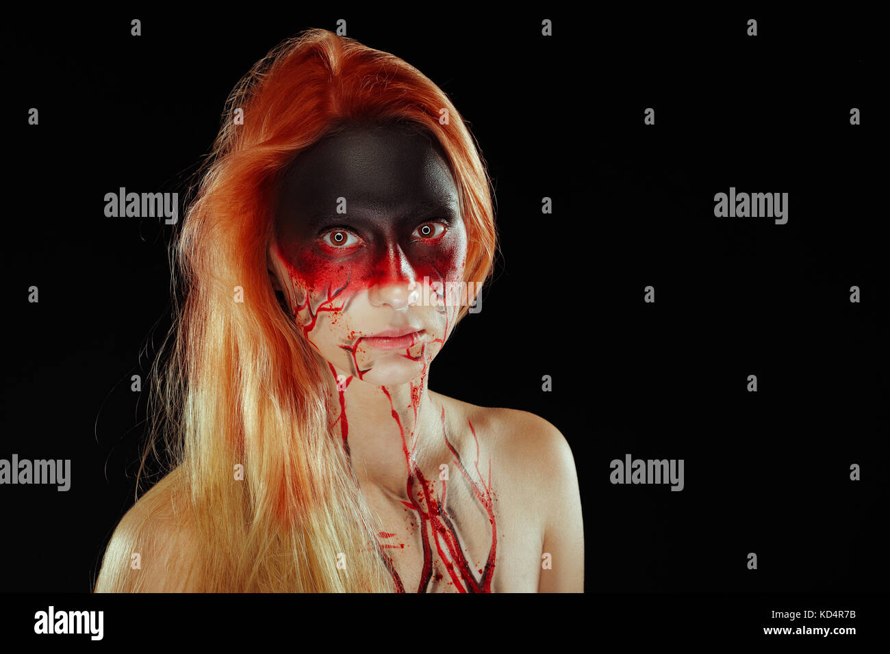 Mystic hero, bloody girl with blood on her face on a dark background. Fantasy horrible and Halloween makeup. Stock Photo