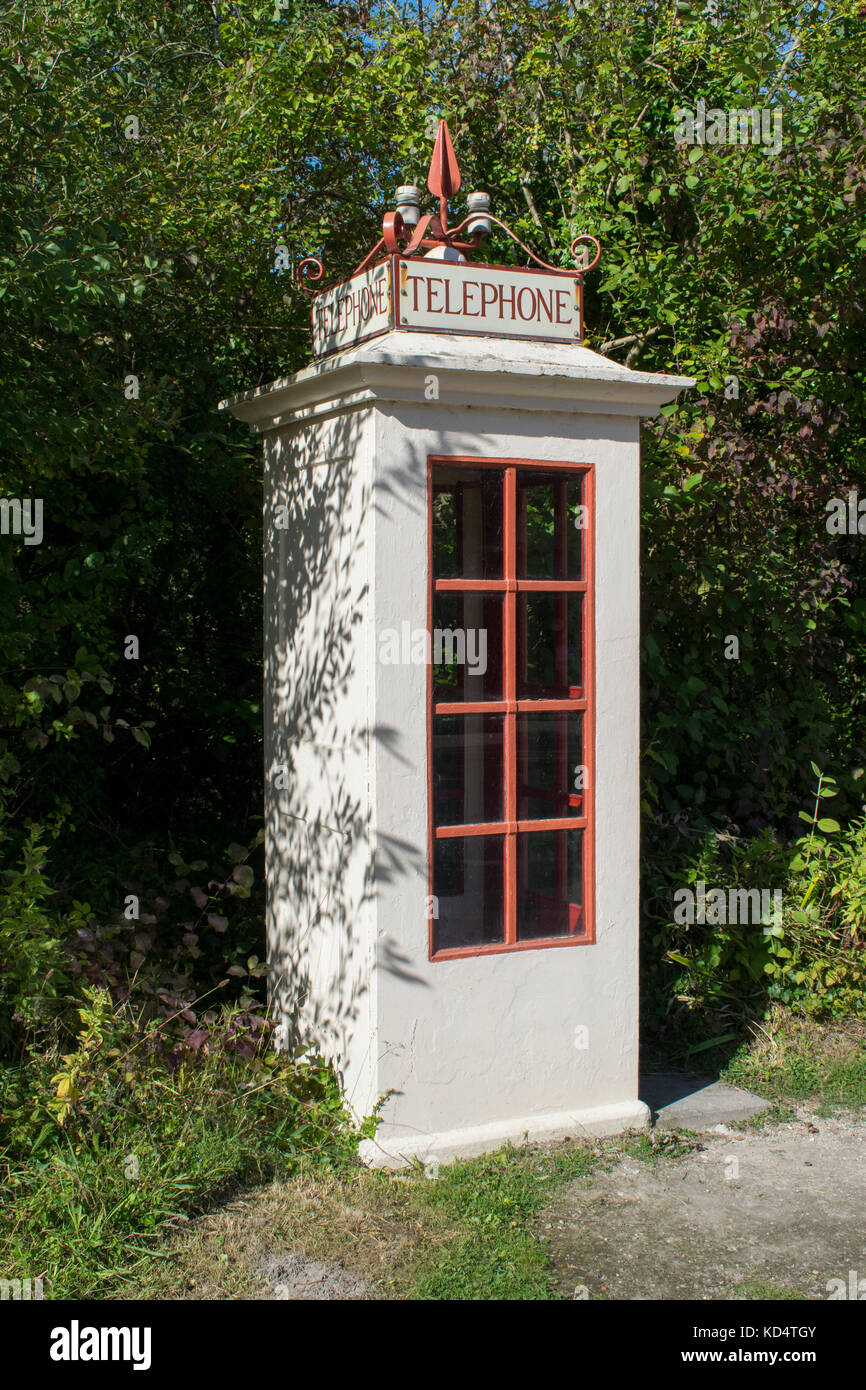 Traditional British K1 red telephone box in a rural setting - Stock Image