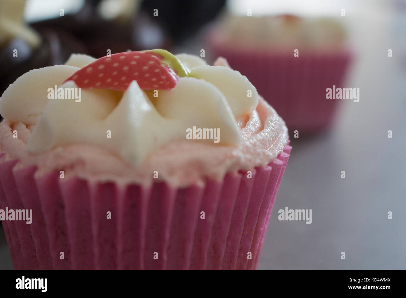 Strawberry and Chocolate Cupcakes Accompanied by Hot Chocolate with Cream and Chocolate dusting. - Stock Image