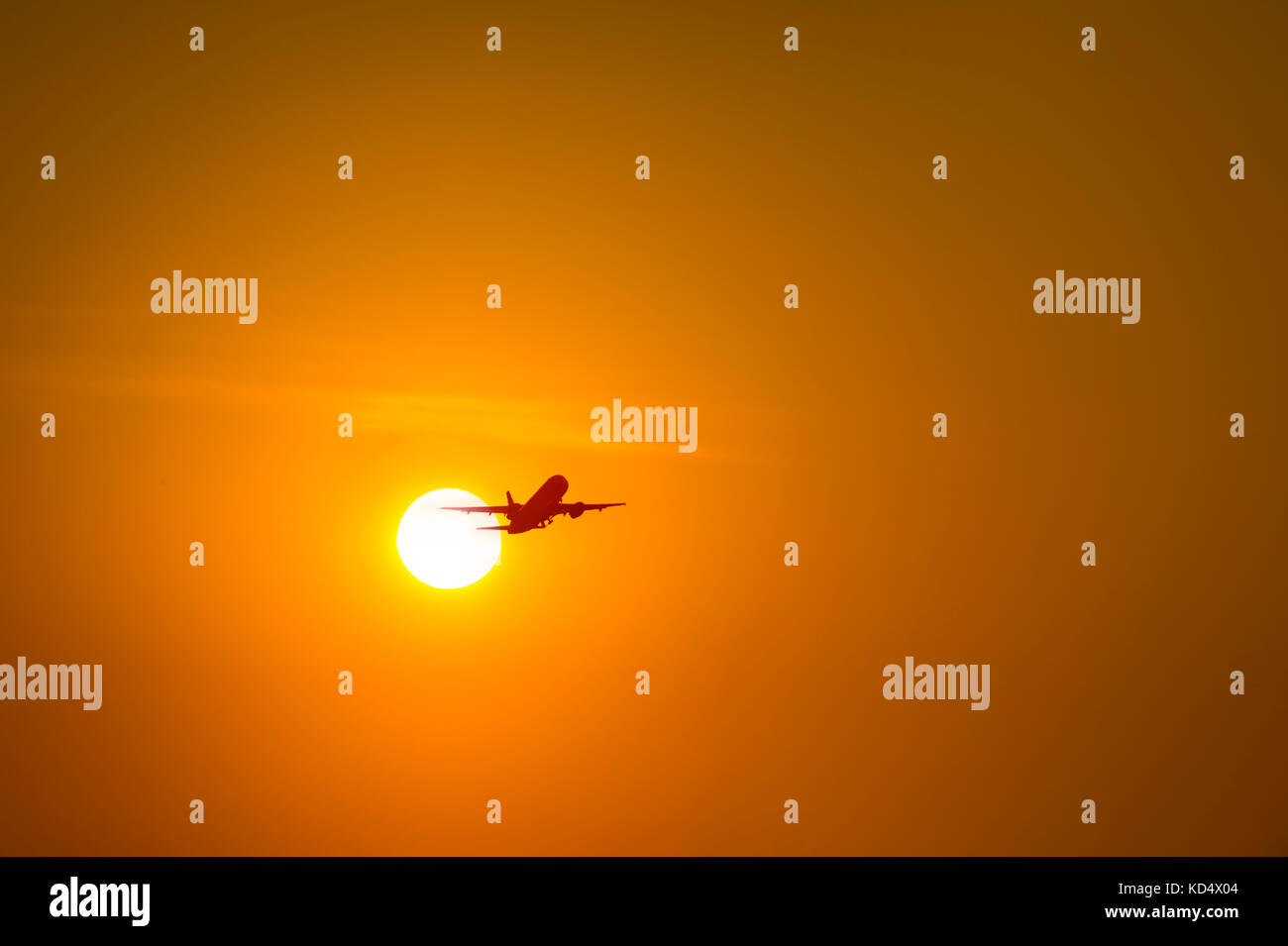 Airplane Flying In Front Of Sun - Stock Image