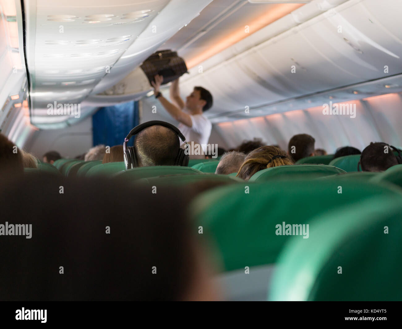 airplane interior - people sitting on seats, wideshot - Stock Image
