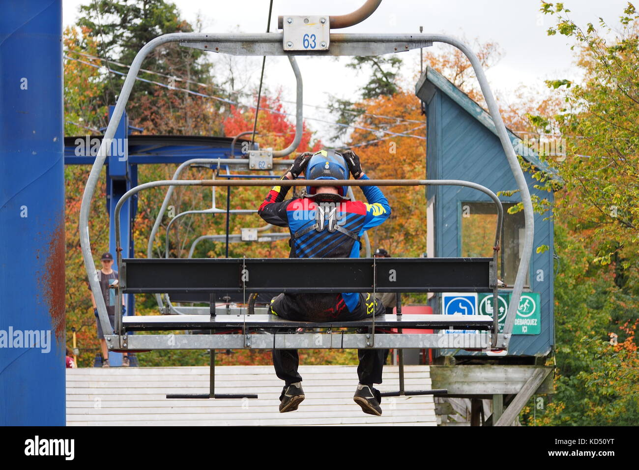 Skyline ski lift carrying a downhill mountain biker up to the trails at Camp Fortune, Gatineau Park, Quebec, Canada.. - Stock Image
