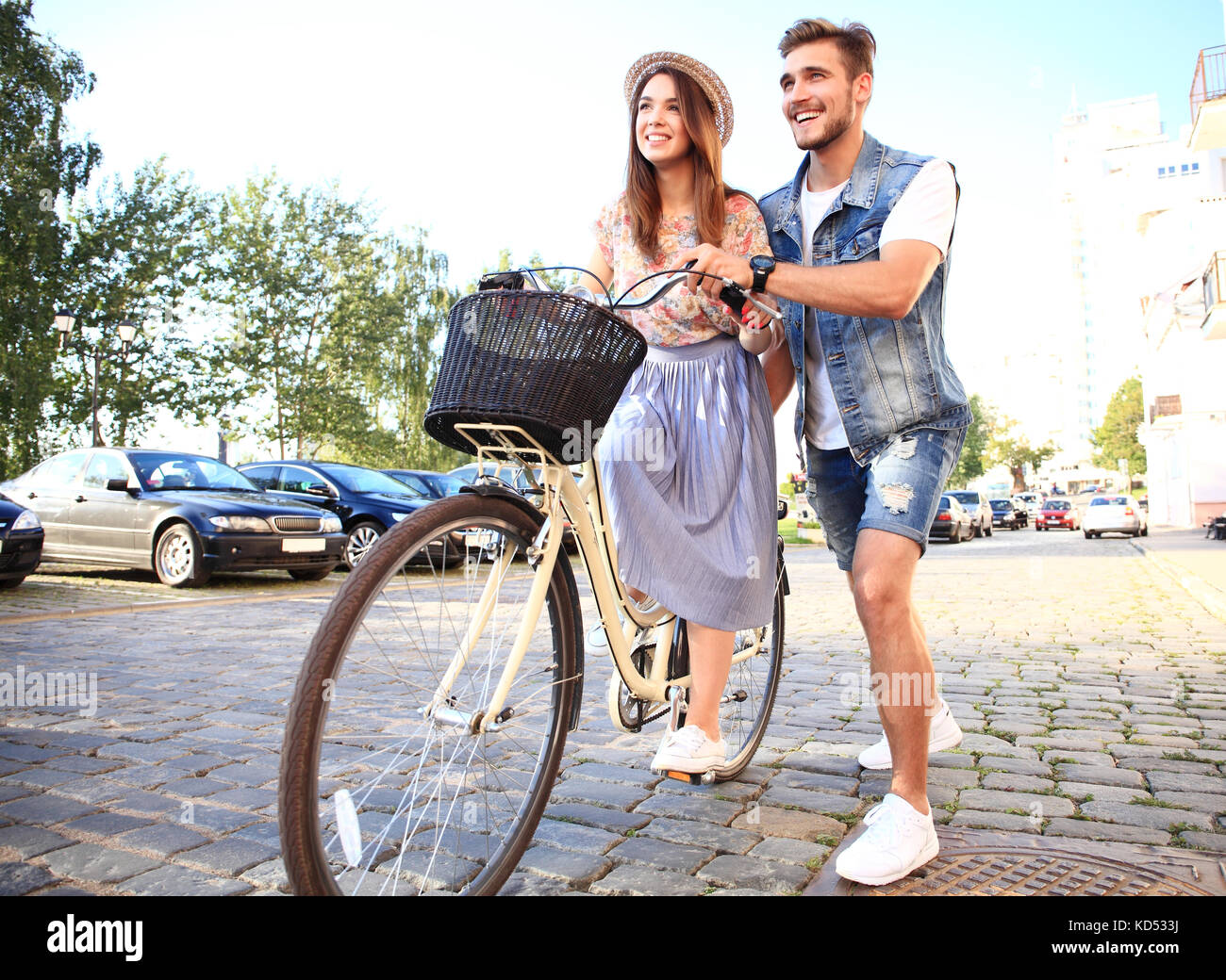 Happy young couple going for a bike ride on a summer day in the city.They are having fun together. - Stock Image