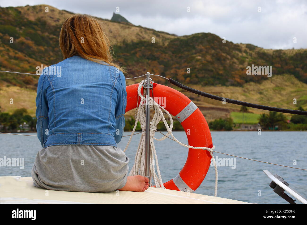 Ile aux Cerfs, Mauritius - unidentified young woman on the deck of a yacht on a blustery day in landscape format - Stock Image