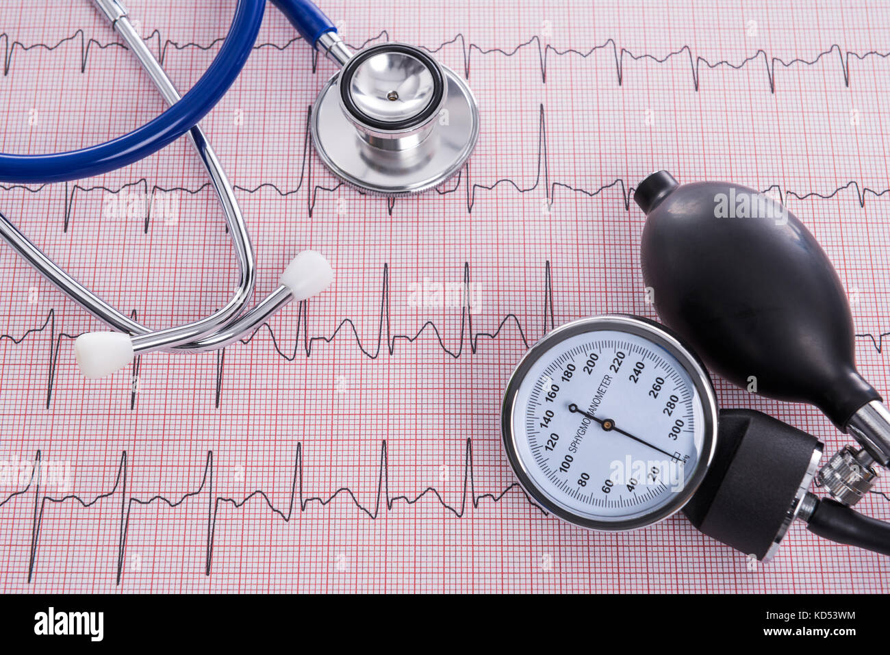 Sphygmomanometer with aneroid gauge and stethoscope with Electrocardiogram paper, still life photo. - Stock Image
