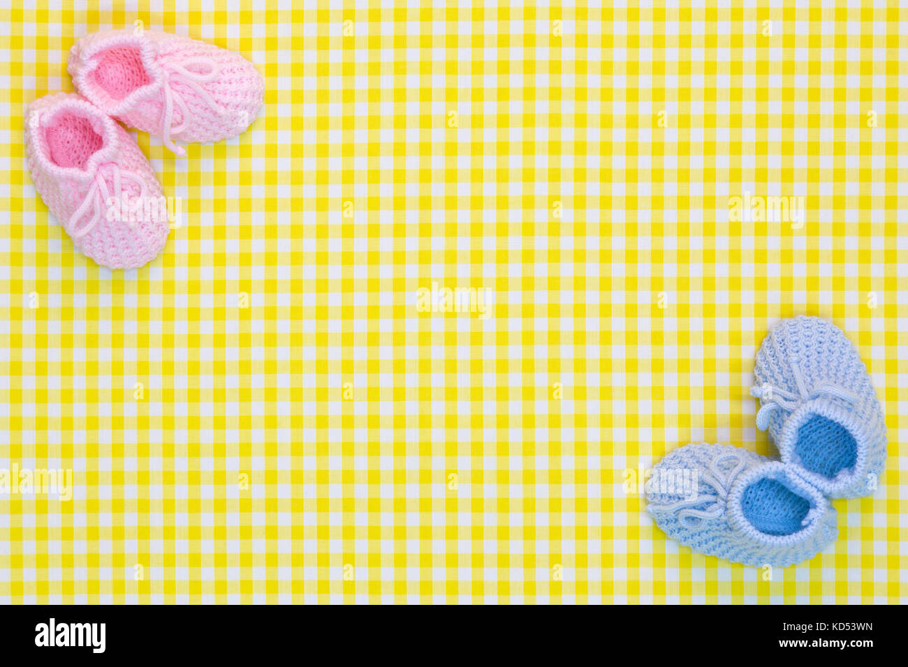 Kinitted Baby booties for a girl and a boy on a yellow gingham background. - Stock Image