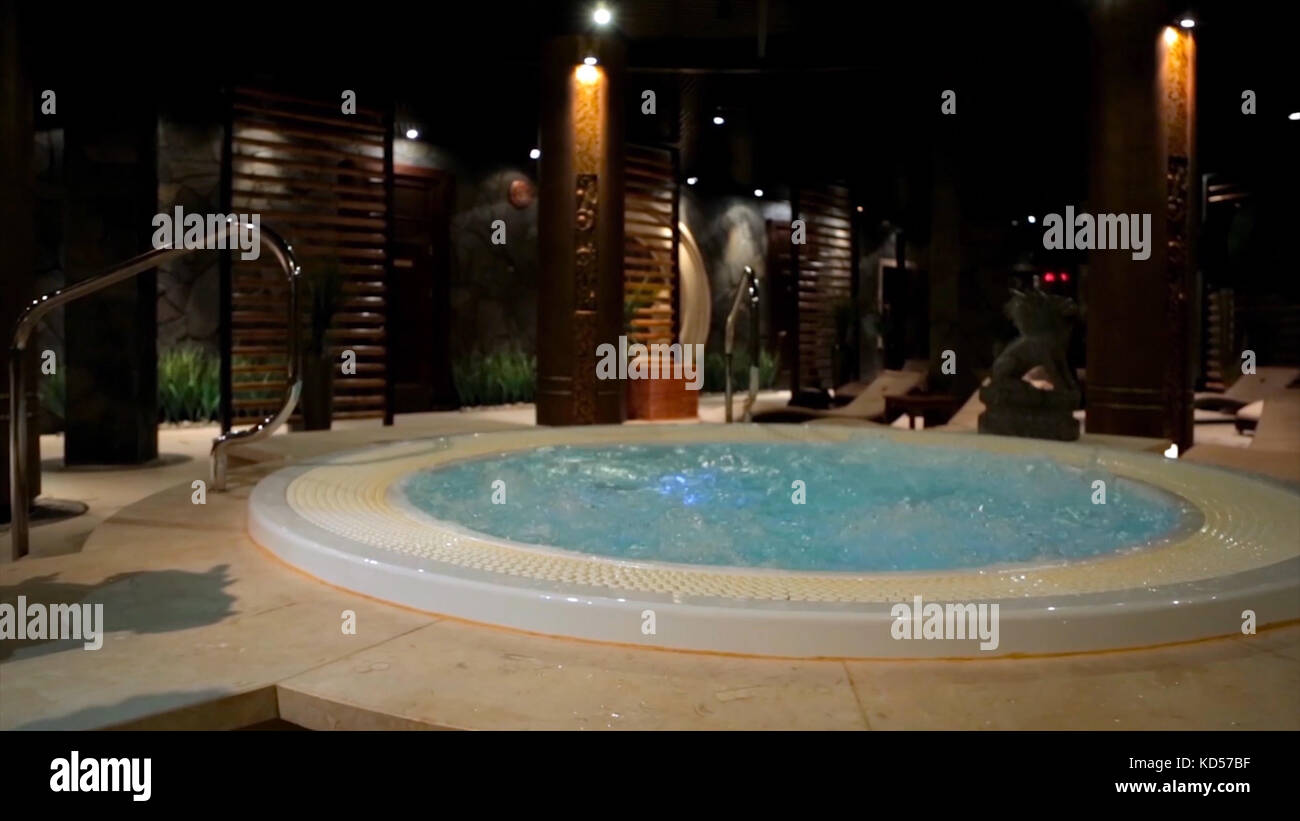 Relaxation pool in spa with waterfall. Empty luxury spa with jacuzzi and swimming pool. Jacuzzi in the sauna. Wellness - Stock Image