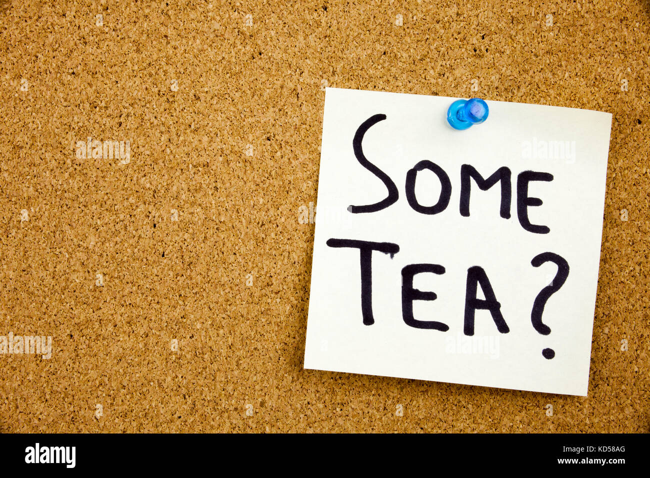 A yellow sticky note writing, caption, inscription Phrase SOME TEA in black ext on a sticky note pinned to a cork - Stock Image