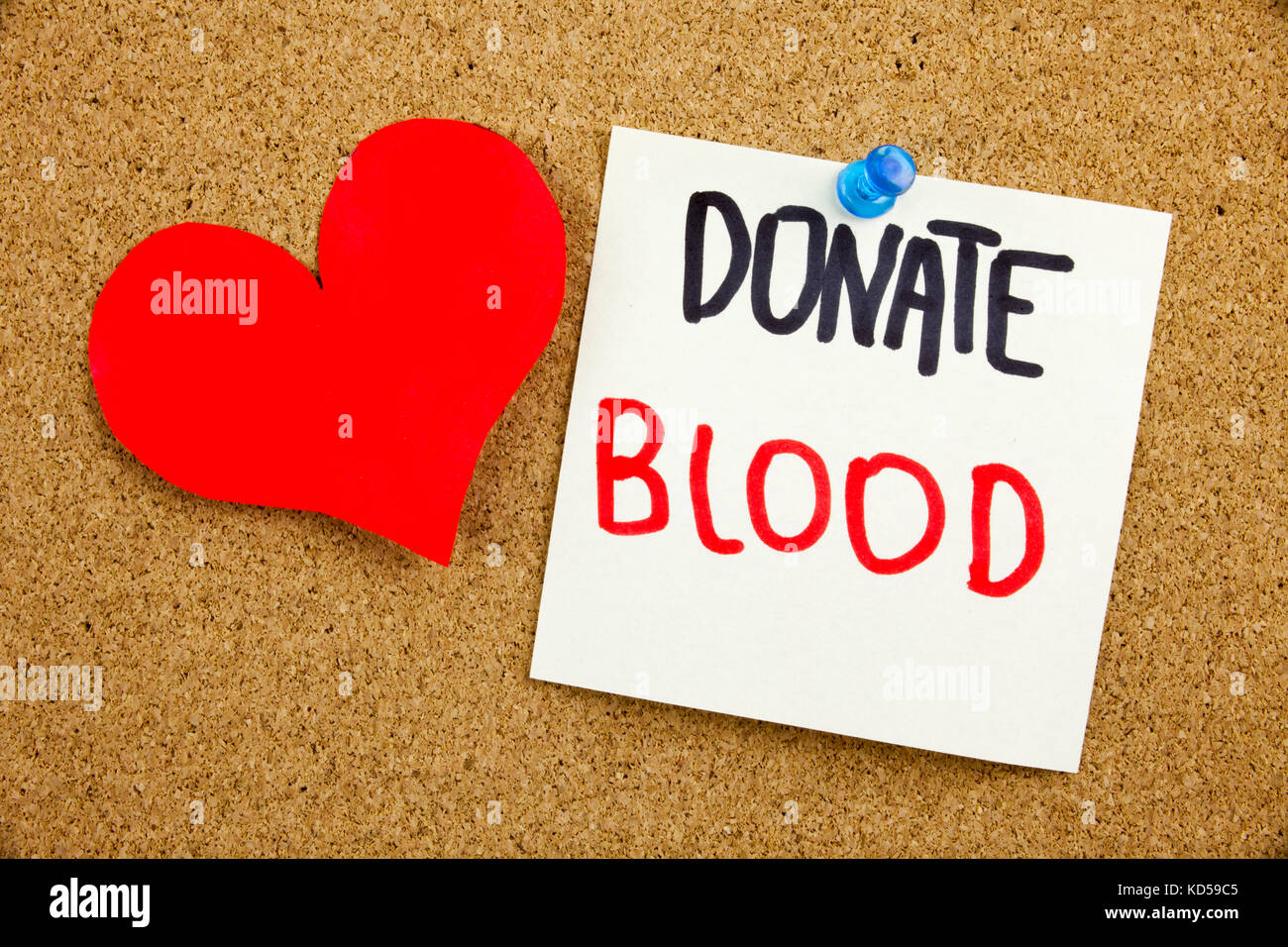 A yellow sticky note writing, caption, inscription Phrase DONATE BLOOD in black ext on a sticky note pinned to a - Stock Image