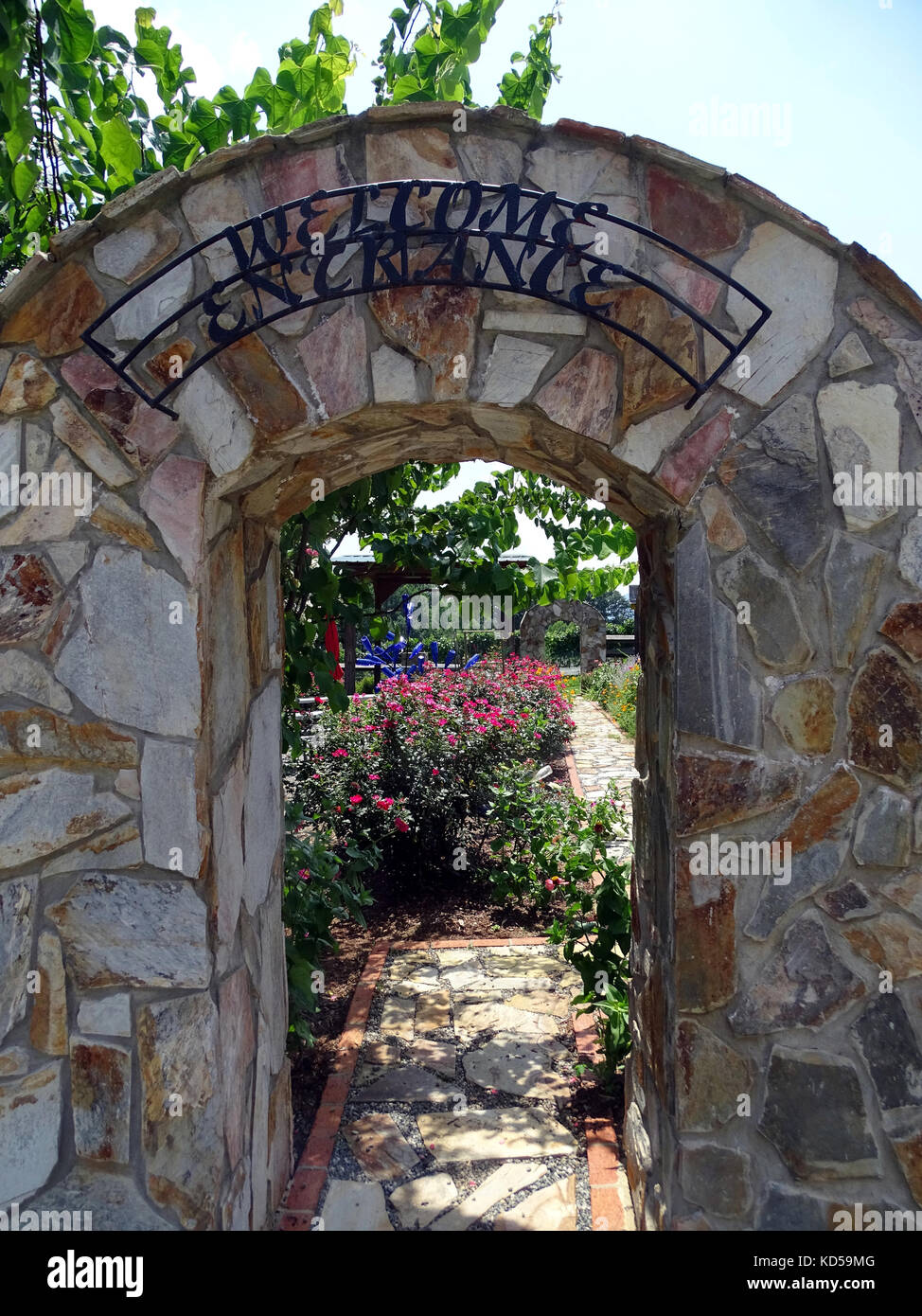 A stone archway serving as an entrance to a winery which is used to welcome guests - Stock Image