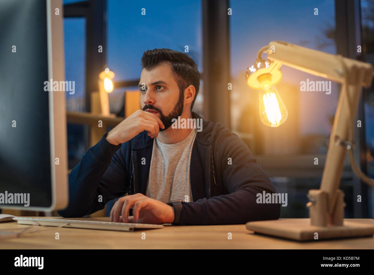 Attentive office worker doing his job - Stock Image