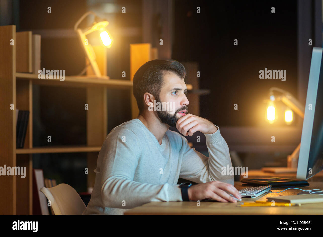Concentrated brunette touching his chin - Stock Image