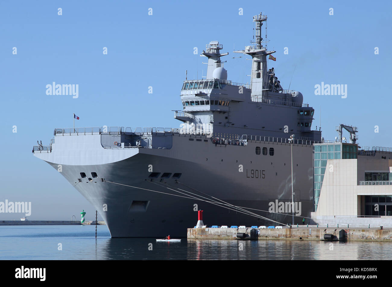 Warship and a man in a skiff rowing boat in Barcelona port Catalunya Spain - Stock Image