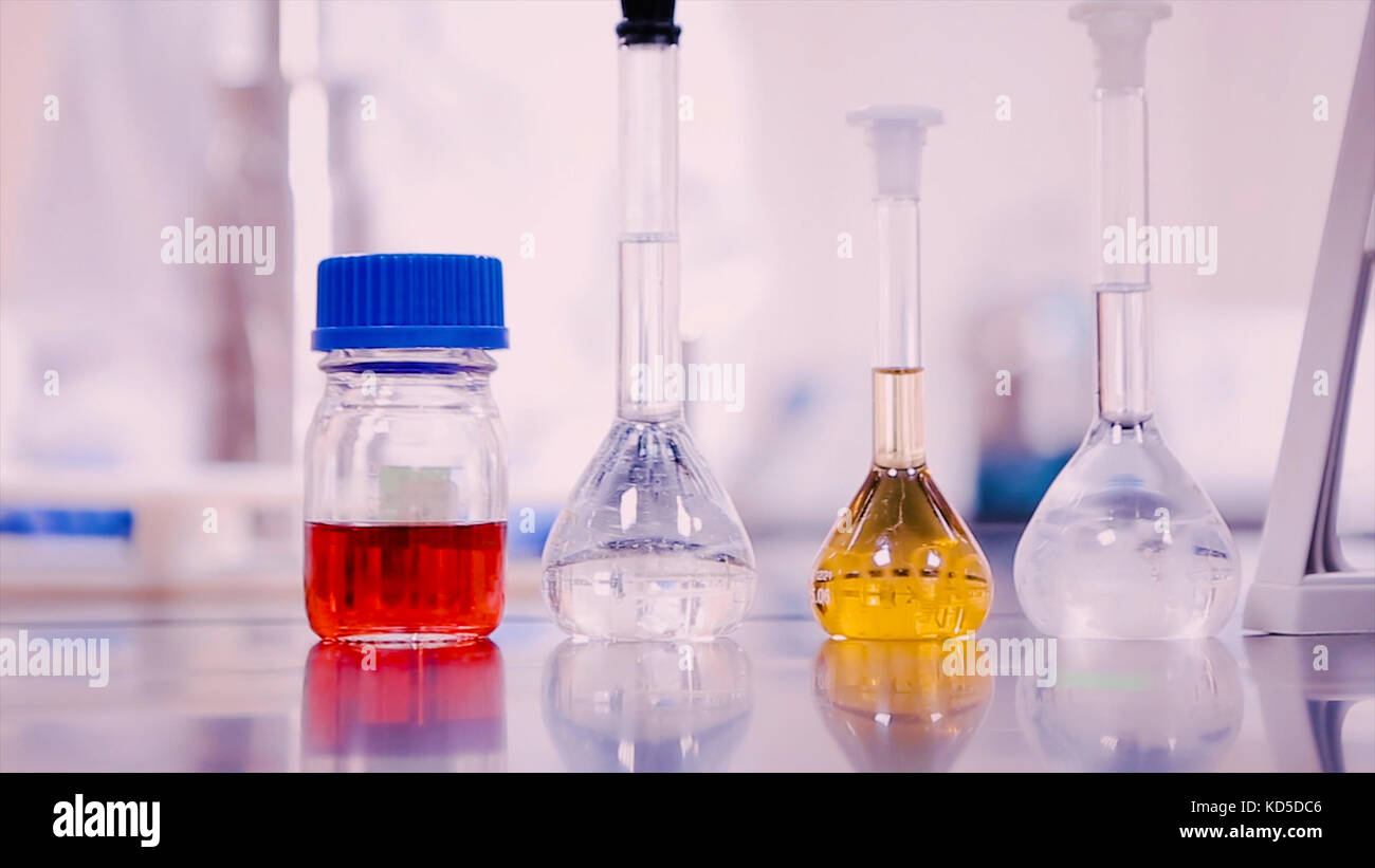 Laboratory flasks and beakers with liquids of different colors on lab table Stock Photo