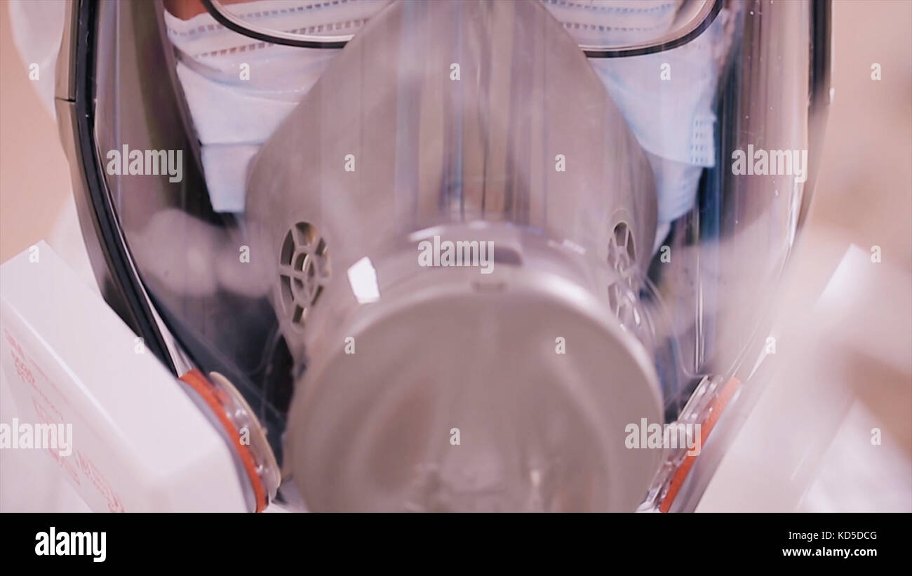 Scientist in protective clothing with respirator. Infection control concept. Scientist in protective suit and gas - Stock Image